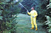 A man wearing protective clothing and a face mask spraying pesticide or insectide