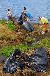 Volunteers clean trash from the side of a harbor as part of a community program to clean up their local wetland.