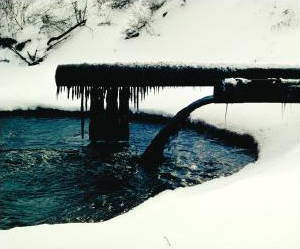 Water pollution pipe pouring against background of snow. US Environmental Protection Agency Great Lakes National Program office